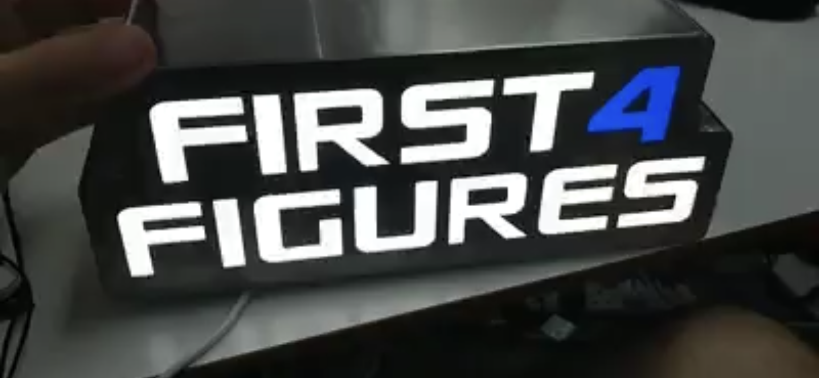 First 4 Figures Logo Sign for New Studio